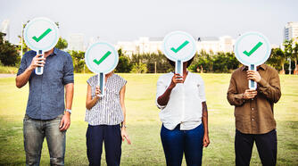 Canva - Four People Holding Green Check Signs Standing on the Field Photography