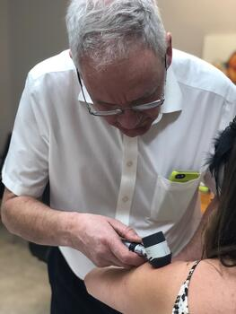 John Pyne performing a skin cancer check with a dermatoscope 2